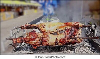 Lambs are roasting on a spit. - Roasting lamb is preparing...
