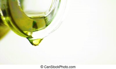 pouring olive oil with macro drops by bottle on brown white...