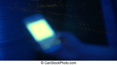 Sms typing by the window at night