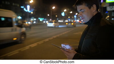 Man using touch pad by the busy road in city