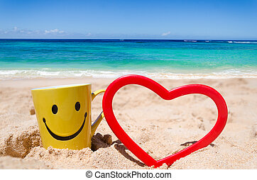 Happy face mug with heart shape on the beach - Happy face...