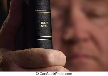 Bible And Face - Christian holds Holy Bible in his hand with...