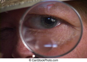 Magnified Male Eye - Man holds a magnifying glass to his eye...