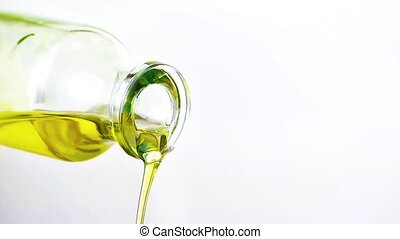 close-up of pouring olive oil with the bottle on white...