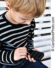 progress is everywhere - little boy using smartphone with...