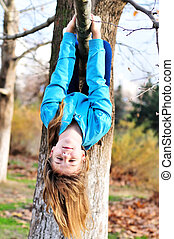 like a sloth - Teen girl hanging on the tree in autumn time...
