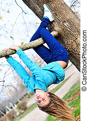 like a sloth - Teen girl hanging on the tree in autumn time,...