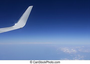 Aircraft wing detail flying high up in deep blue sky