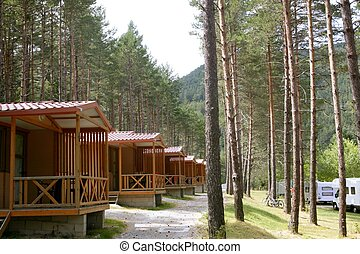 Forest wooden cabins in a mountain camping