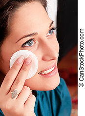 Young woman removing makeup with cleansing pad