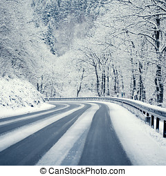 Winter Scenery - Curvy snowy country road leading through a...