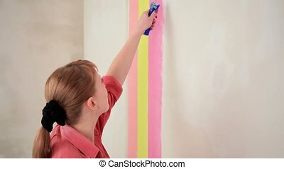 The Girl Paints A Wall With Color Strips