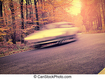 Autumn Driving - Car driving on a curvy road in autumn -...