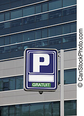 Parking signpost with gratuit text and modern building...