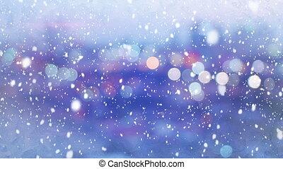 defocused lights evening wintry city and snowfall loop -...