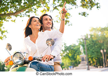 Smiling young couple on scooter together while woman...
