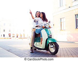 Happy young couple on scooter together while woman pointing...