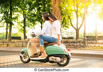 Young couple riding a scooter in town