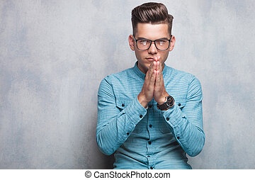 young casual man praying against grey studio background