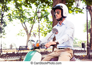 Man in helmet riding on scooter - Young man in helmet riding...