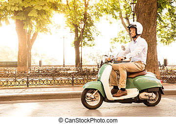 Trendy man driving a scooter in helmet Sun is shining...