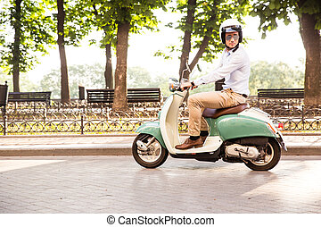 Trendy man driving a scooter in helmet in old town