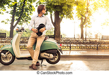 Stylish man standing near his scooter with helmet in his...