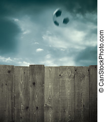 Wooden Fence and Soccer Ball - A wooden fence in front of a...