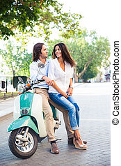 Happy young couple on scooter looking at each other outdoors