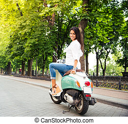Happy young woman on a scooter