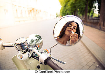 Closeup of a female applying lipstick in mirror motocycle