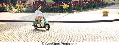 Handsome young man driving scooter in old european town