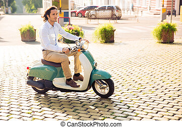 Happy young man riding on scooter in the city