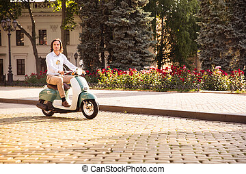Confident young man riding a scooter through town streets in...