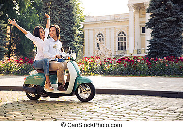 Happy young couple traveling in scooter in old european city