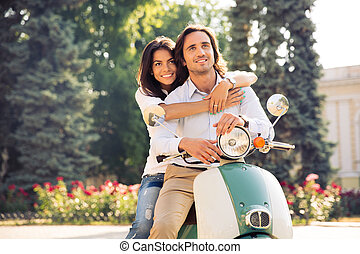 Happy romantic couple hugging on scooter