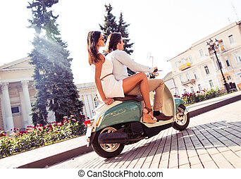 Young couple riding a scooter in old european town