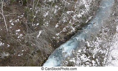 River and snowfall - Flow of blue river and snowfall in late...