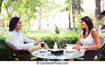 Young beautiful couple drinking coffee and having romantic...