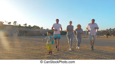 Sportive family running on the beach - Steadicam shot of big...