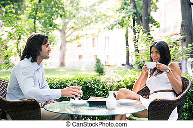 Happy beautiful couple drinking coffee and having romantic...