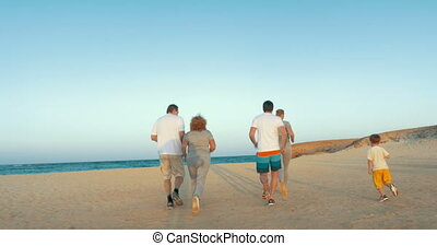 Family running to sea in the evening