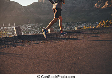 Young man running on country road - Low section image of...