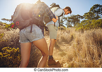 Couple hiking in mountain on a hot sunny day - Hiker helping...