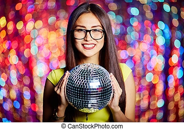 Disco queen - Posh girl with disco ball looking at camera in...
