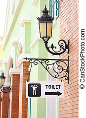 toilet sign hanging on brick wall and vintage lamp