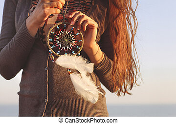 Brunette woman with long hair holding dream catcher in her...