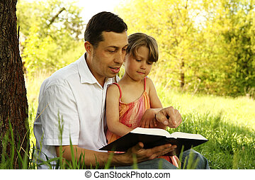 young father with his little daughter reading the Bible - a...