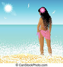 Young woman stands on the beach at sunset time.