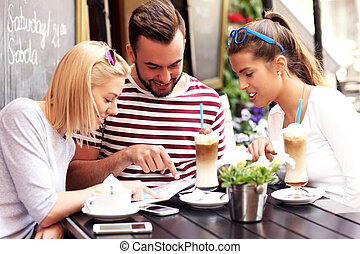 Group of tourists looking at map in a cafe